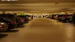 People in full underground parking garage with lots of cars