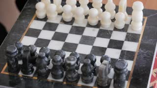 People playing chess on a black and white chess board