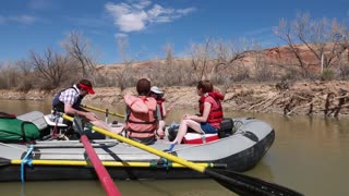 people river rafting on san juan river by cliff