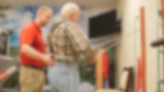 Physical Therapist Helps An Old Man In A Retirement Home Gym Out Of Focus