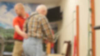 Physical Therapist Helps An Old Man In A Retirement Home Gym