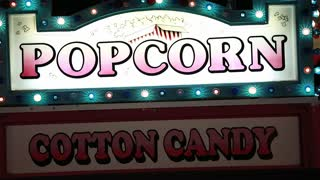 popcorn and cotton candy sign at carnival