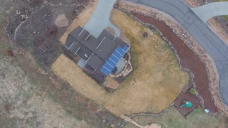 Rotating aerial shot of a home with solar panels on roof