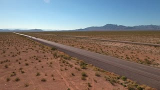 Rotating aerial shot of vehicles on a long highway in a desert