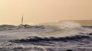 Sailboat and Surfers During Sunset