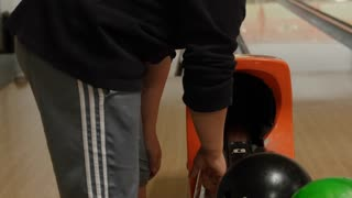 Shot of a boy bowling at a bowling alley