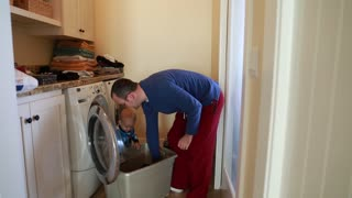 single father doing laundry with his toddler
