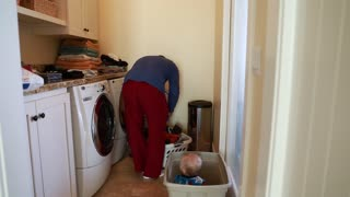 single father doing the laundry with his toddler boy