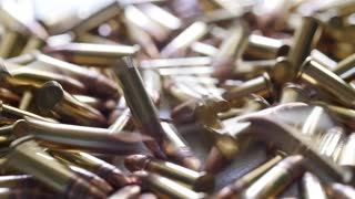Slow motion a dolly shot of a pile of .22 ammunition bullets