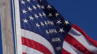 Slow motion American flag blows in strong wind closeup