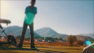 Slow motion boy playing golf on the golf course