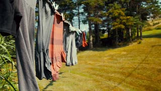 Slow motion clothes drying on the line blowing in a wind