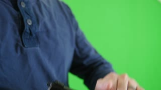 Slow motion green screen shot man loading bullet in pistol chamber