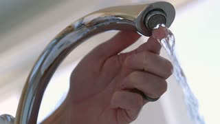 Slow motion man turns off bathtub faucet