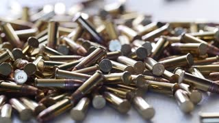 Slow motion of a dolly shot of pile of .22 ammunition bullets