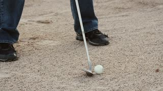 Slow motion of a man hitting a golf ball out of sand trap