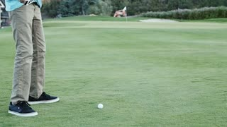 Slow motion of a man hitting a golf ball with his golf club on course