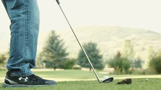 Slow motion of a person hitting a golf ball on a golf course
