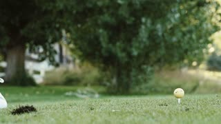 Slow motion of a teenager hitting a golf ball on the golf course