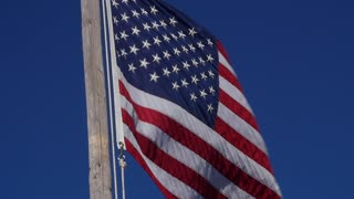 Slow motion of American flag blows in strong wind closeup