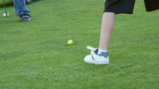 Slow motion of boy hitting the golf ball with his golf club on course