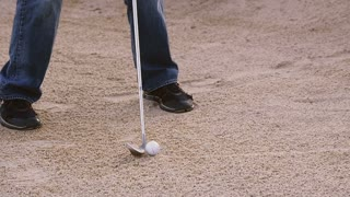Slow motion of man hitting a golf ball out of sand trap