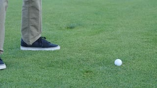 Slow motion of man missing a golf ball with his club