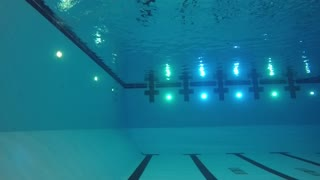 Slow motion of swimmer cannon ball into pool underwater side shot