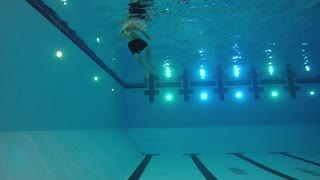 Slow motion of swimmer exiting pool underwater side shot