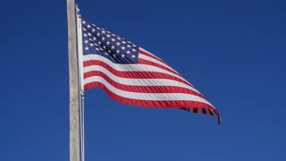 Slow motion of the American flag blows in strong wind closeup