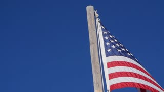 Slow motion of the American flag blows in strong wind panning