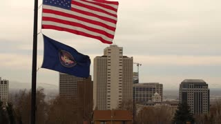 Slow Motion of the United States Flag at half mast and city