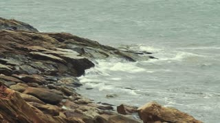 Slow motion shot of a very rocky beach and the rough ocean water