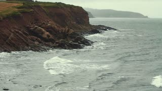Slow motion shot of a very rocky shore cliffs and the rough ocean water