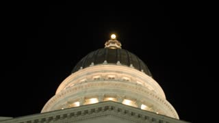 The lights on Utah State Capitol dome with flags tilting shot