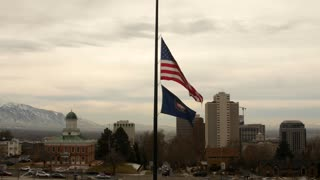 The United States Flag flies at half mast over city