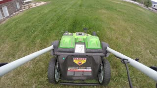 Timelapse handlebar and lawn mower mowing tall grass on the lawn