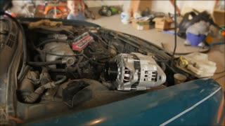Timelapse of men putting an alternator in car