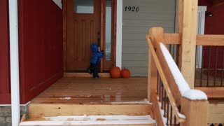 toddler and mother playing on home patio outside in snow