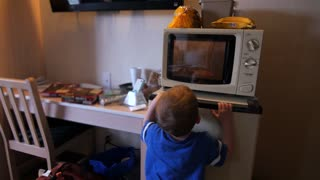 Toddler watching pizza cook in hotel microwave