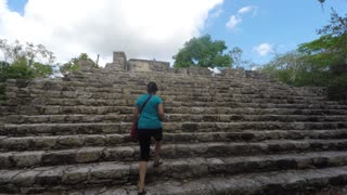 Tourist climbing stairs in ancient Mayan ruins at Coba