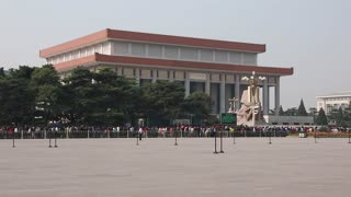tourists in tiananmen square waiting in line to see mao zedong