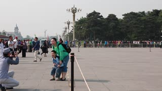 tourists in tiananmen square waiting to see mao zedong