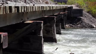 Train bridge over flooding river in mountains