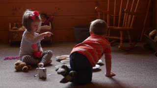 Two little kids playing house together at home