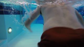 Underwater pool shot man swimming breastroke laps