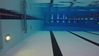 Underwater pool shot of a man swimming toward camera