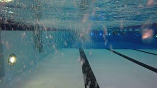 Underwater pool shot of a man walking toward camera
