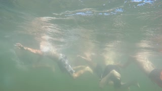 Underwater shot kids swimming in mountain lake