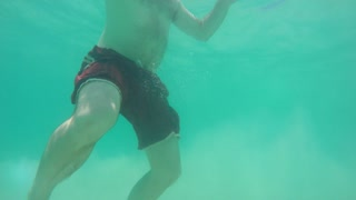 Underwater shot of a man swimming in caribbean water